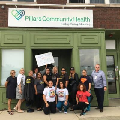 Photo of a group of Pillars Community Health members standing outside of a building