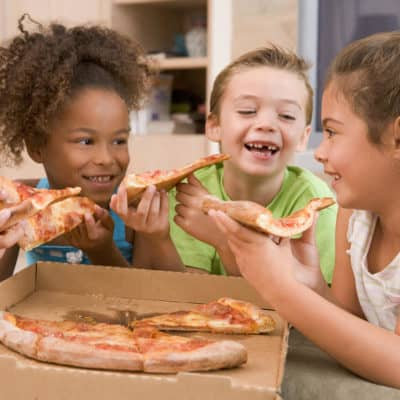 Photo of young kids eating pizza