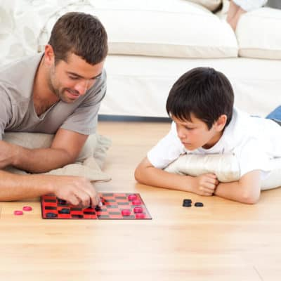 Photo of a volunteer playing checkers with a young man