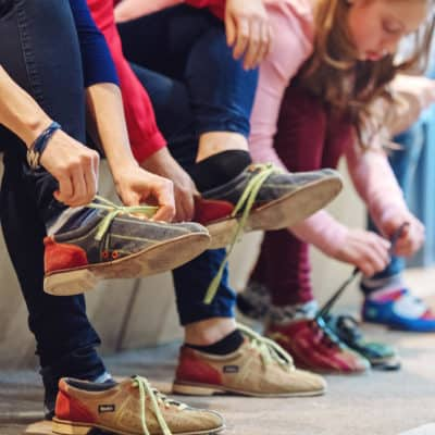 Photo of a group of people lacing up bowling shoes