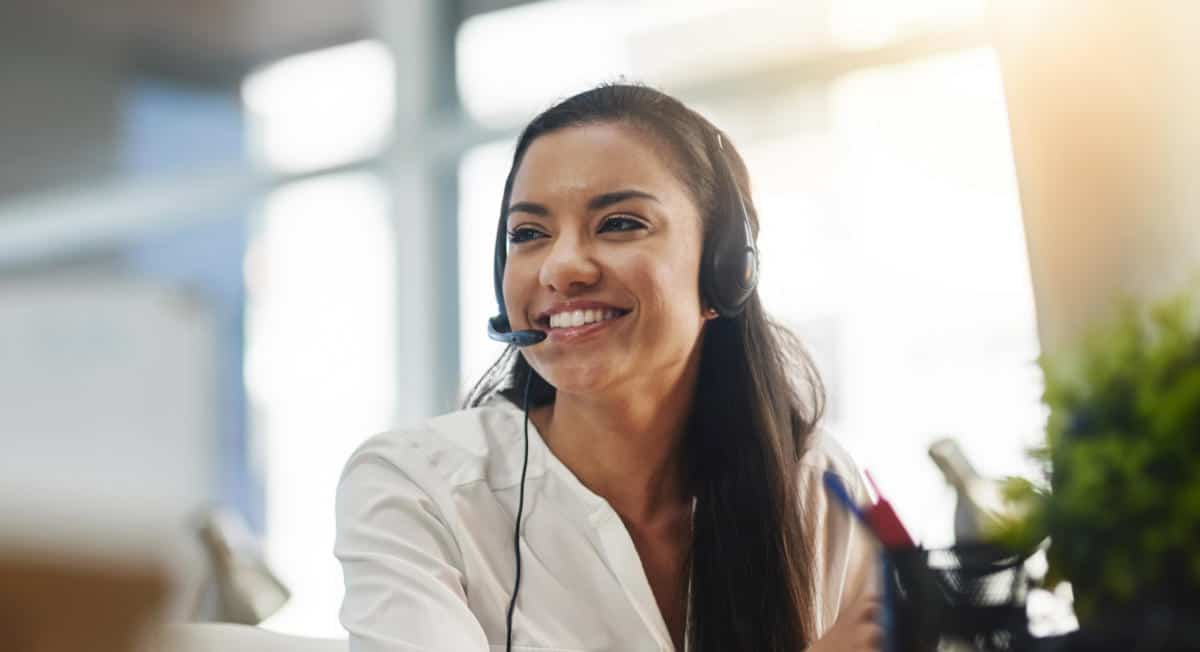 Photo of a brown woman wearing a headset