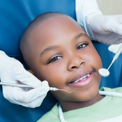 Photo of a young boy having his teeth cleaned at the Dentist