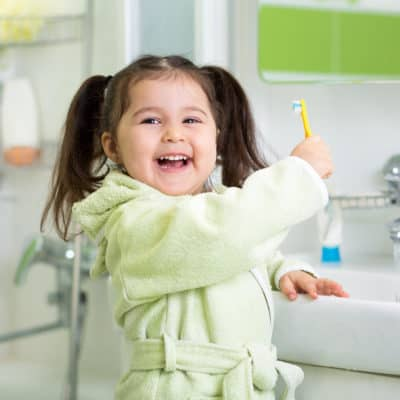 Photo of a young girl smiling while holding a toothbursh