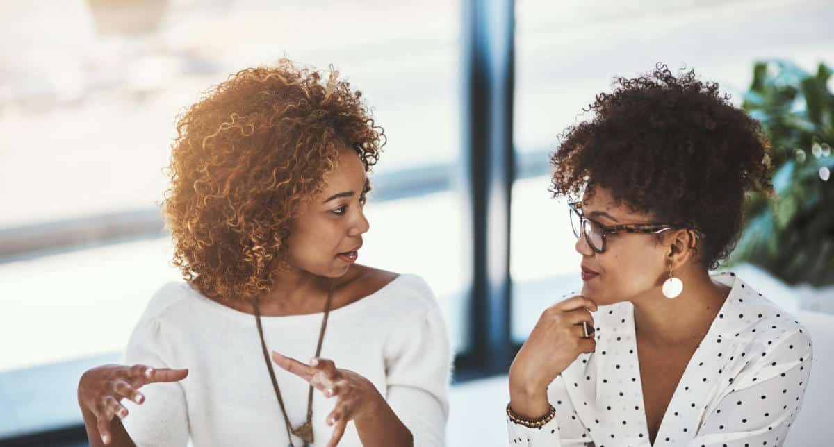 Photo of two woman talking with each other