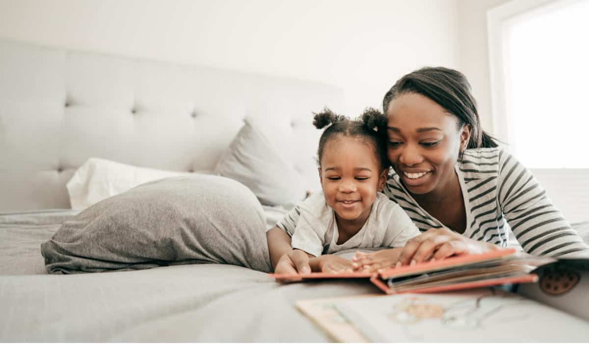 Photo of an African American Mother and daughter reading in bed