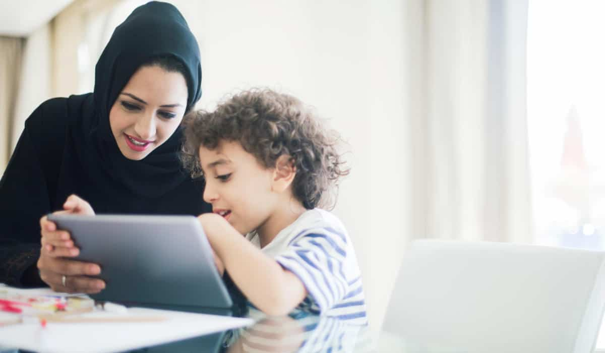 Photo of an Arab Mother and son playing with an iPad