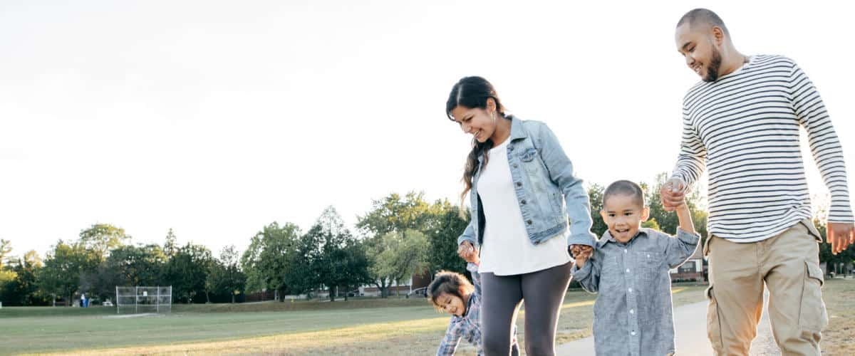 Photo of a hispanic family walking through a park