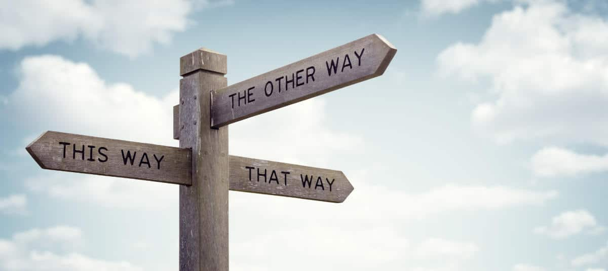 "Photo of a wood crossroads sign that says ""This Way,"" ""That Way,"" and ""The Other Way"""