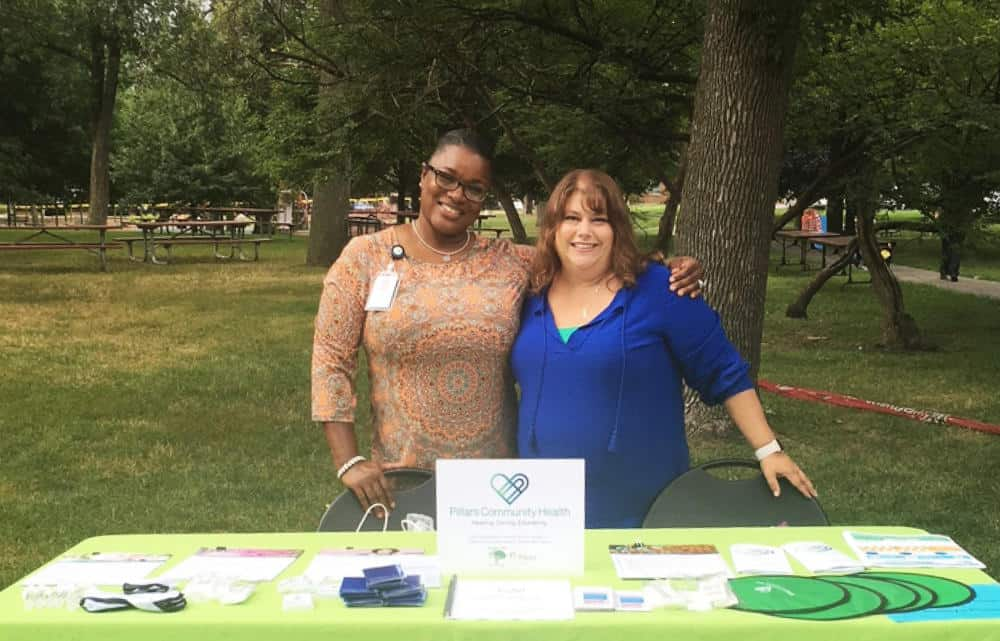 Photo of Volunteers in Park Standing by a Pillars Community Health Table