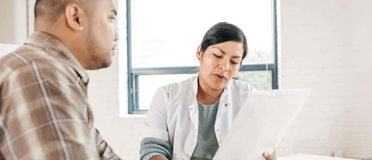Photo of a female doctor reading financial documents with patient