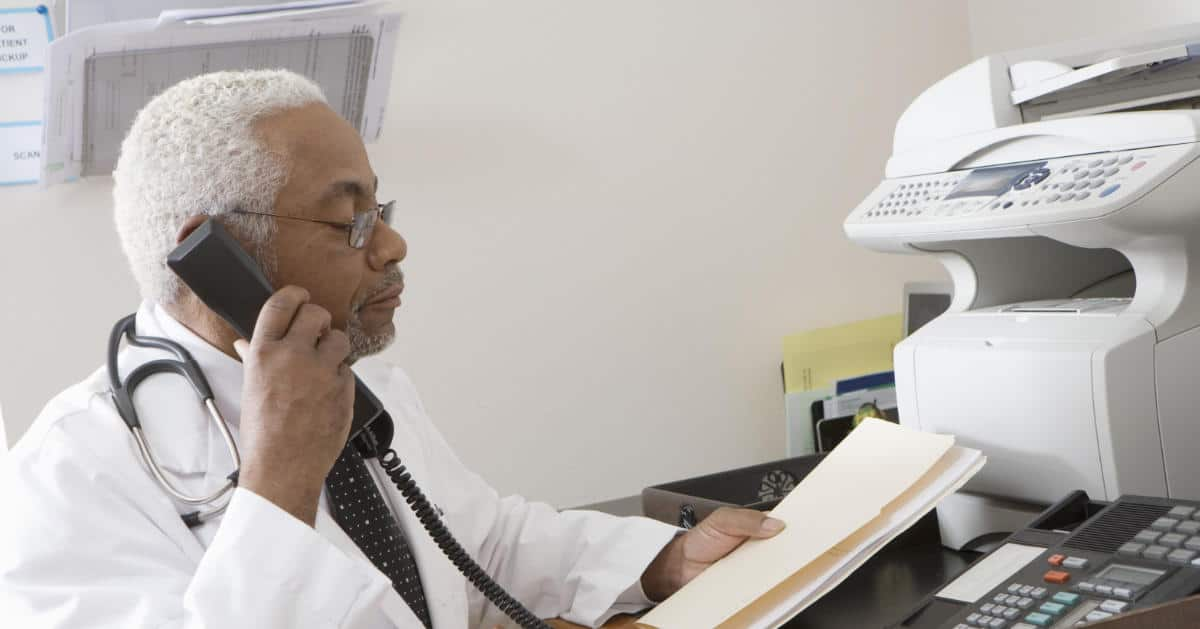 Photo of a Doctor talking on the phone while holding patient records